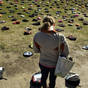 ORG XMIT: VTBUR101 In this Tuesday, April 19, 2011 photo, Ashley Koetsier, 21, of Woodstock, Vt., reads about a college student who died by suicide from a small laminated plaque attached to a backpack on the green outside Davis Center at the University of Vermont in Burlington, Vt.  Active Minds, a student group dedicated to promoting increased dialogue about mental health and incidents and impacts of sucide, placed 1,100 backpacks representing victims, dozens with personal stories of student suicide. (AP Photo/The Burlington Free Press,  Ryan Mercer) MAGS OUT; NO SALES; MANDATORY CREDIT TV OUT