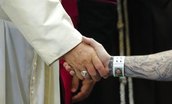 Pope Francis clasping hands with an inmate at a Philadelphia prison yesterday.