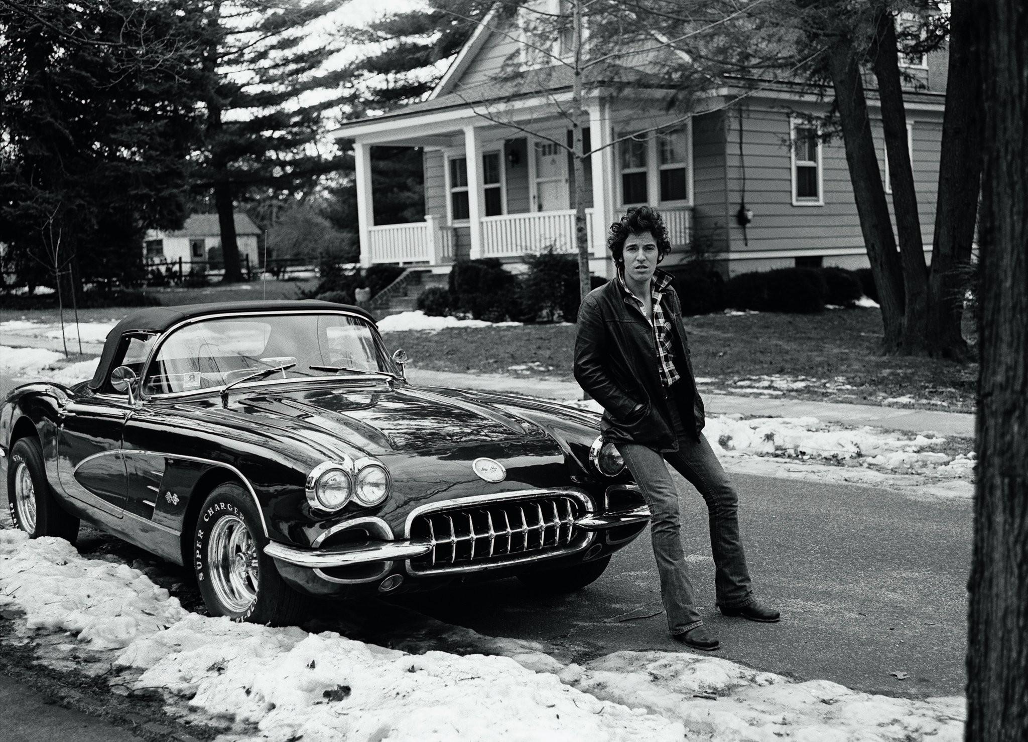 Bruce Springsteen sitting on a corvette